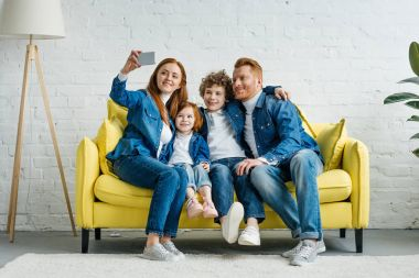 Happy family taking selfie while sitting on sofa