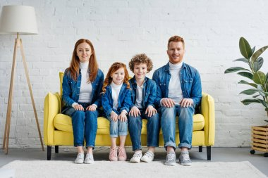 Smiling family with kids sitting on sofa in room