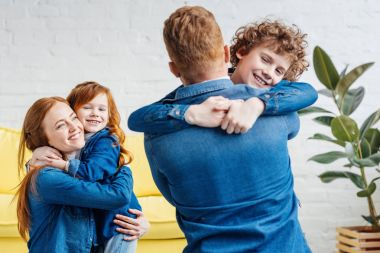 Cute family parents and children embracing at home