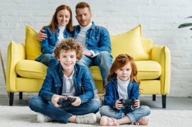 Children playing video game while parents sitting on sofa