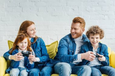 Kids and parents playing video game while sitting on sofa