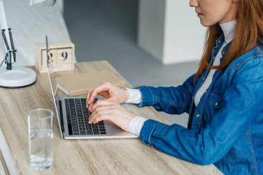 Woman typing on laptop at working table