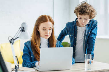 Child standing by woman working with laptop at table
