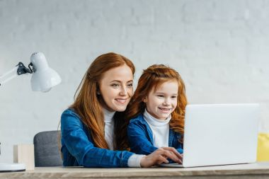 Woman and child looking at laptop screen