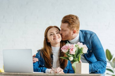 Man giving a bouquet of tulips to young woman working by laptop