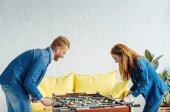 Mladý šťastný pár hrát stolní fotbal