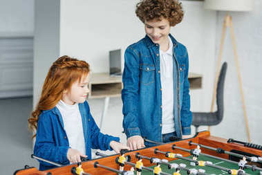 Cute children playing table football together
