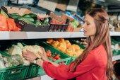 Fényképek kiválasztása friss nyers zöldségeket, élelmiszerbolt nő oldalnézetből