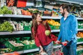 smiling couple with shopping cart shopping together in supermarket