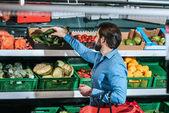 Fotografie muž s nákupní košík výběrem čerstvé zeleniny v obchodu s potravinami