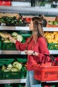 Fotografie ženská volba čerstvou syrovou zeleninu v obchodě