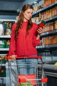 Fotografie woman with shopping trolley choosing products in supermarket