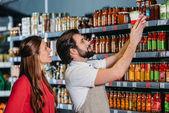 portrét prodavače v zástěře pomáhá ženské shopper v hypermarketu