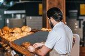 zadní pohled na mužské prodavače uspořádání čerstvý chléb v supermarketu