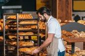Fényképek férfi bolti eladó a kötény intézi friss péksütemények szupermarketben