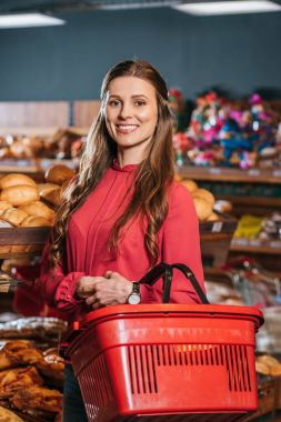 portrait of smiling woman with shopping basket looking at camera in supermarket