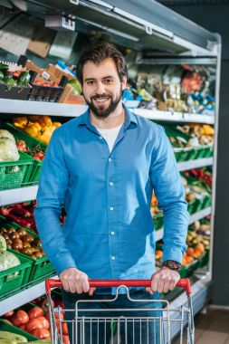 portrait of smiling man with shopping cart in grocery shop