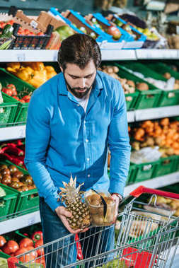 portrait of man putting fruits into shopping trolley in grocery shop