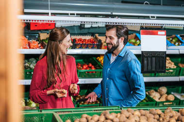 portrait of happy couple shopping together in supermarket