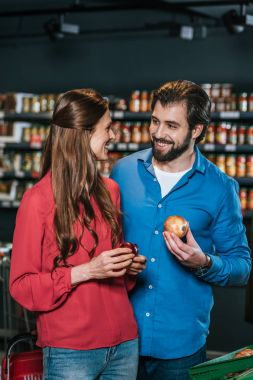 portrait of smiling couple shopping together in supermarket