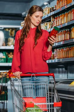 woman with shopping trolley choosing products in supermarket