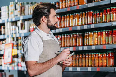 side view of shop assistant in apron with notebook in supermarket