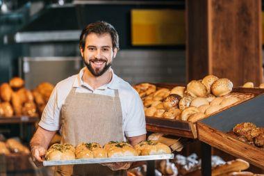 portrait of smiling shop assistant arranging fresh pastry in supermarket