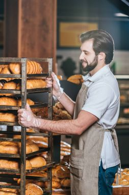 smiling male shop assistant arranging fresh pastry in supermarket