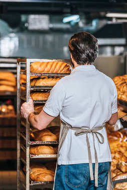 back view of shop assistant in apron arranging fresh pastry in supermarket