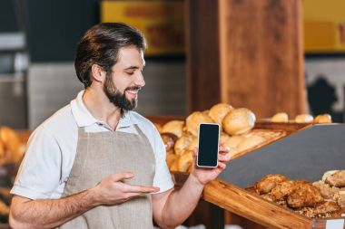 portrait of smiling shop assistant showing smartphone with blank screen in supermarket