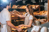 Fotografie shop assistants arranging loafs of bread in supermarket