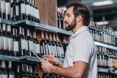 boční pohled na prodavače s tabletem, při pohledu na lahve vína v hypermarketu
