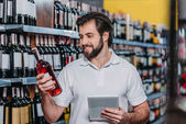 portrét s úsměvem prodavače s tabletem, při pohledu na láhev vína v hypermarketu