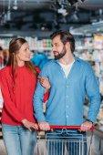 Fotografia Ritratto di coppia con carrello shopping insieme a supermercato