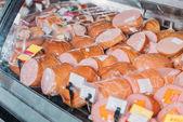 Fotografie zblízka pohled na připravené klobásy a wurst v supermarketu