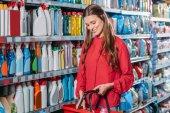 Fotografie portrét usmívající se žena s nákupního košíku v supermarketu