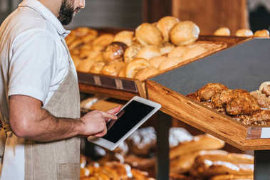 cropped shot of shop assistant in apron using tablet with blank screen in supermarket