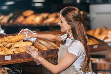 side view of shop assistant arranging loafs of bread in shopping market