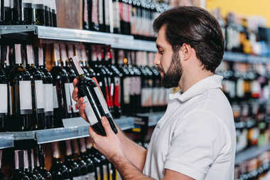 male shop assistant arranging alcohol in supermarket