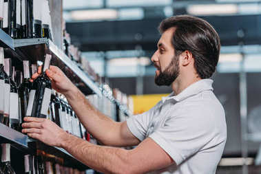 male shop assistant arranging alcohol in supermarket