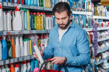 portrait of man putting detergent into shopping basket in supermarket