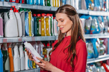 portrait of woman choosing detergent in supermarket