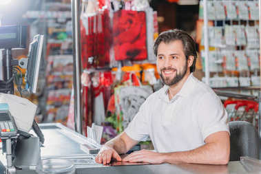 portrait of smiling male shop assistant at cash point in supermarket