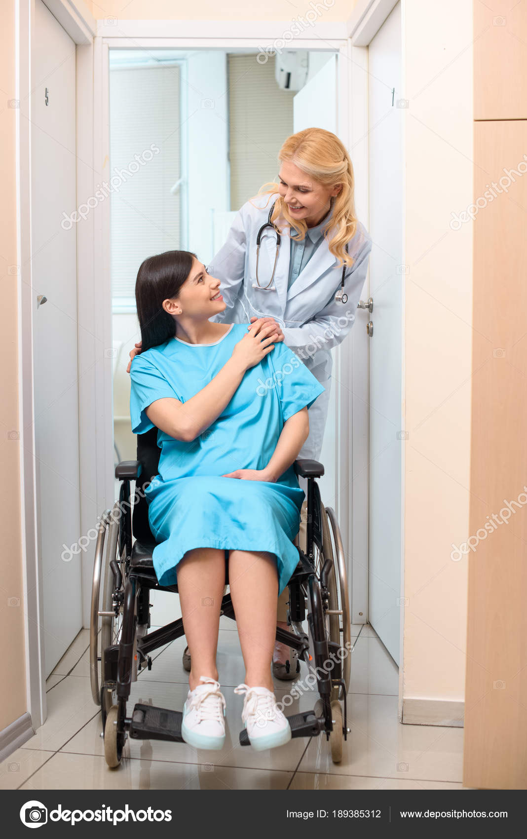 mature obstetrician gynecologist riding pregnant woman wheelchair