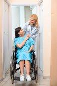 Fotografie Reife Geburtshelfer Gynäkologen Reiten schwangere Frau im Rollstuhl am Krankenhaus und unterstützen Sie