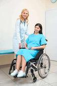 Fotografie Frauenarzt Geburtshelfer und schwangere Frau im Rollstuhl am Krankenhaus
