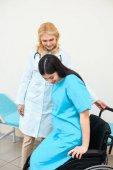 Fotografie Geburtshelfer Gynäkologen hilft schwangeren Frau im Rollstuhl sitzen