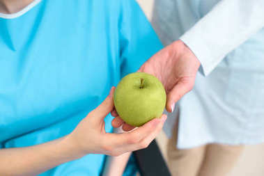 cropped shot of doctor passing green apple to pregnant woman on wheelchair