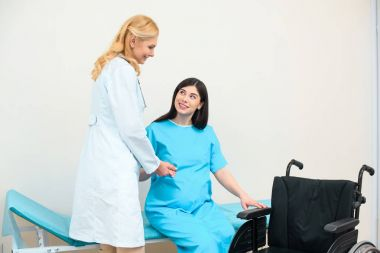 obstetrician gynecologist helping pregnant woman to get to wheelchair