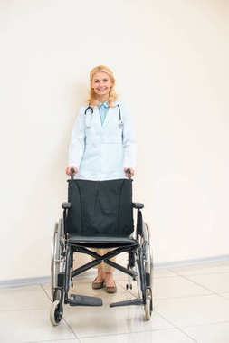 adult female doctor with wheelchair looking at camera
